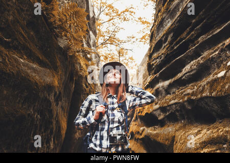 Travel young woman wearing brown hat, plaid shirt, jeans and brown boots with backpack looking up in the wonderful canyon with moss on rocks after hiking, travelling concept