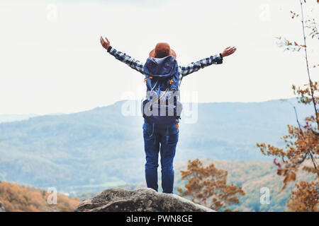 Young travelling woman wearing brown hat, plaid shirt, jeans and brown boots with backpack staying on the stone around the trees, raised her hands up and looking on great forest and rocks views after hiking, travelling concept - Stock Photo