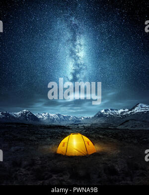 Camping in the wilderness. A pitched tent under the glowing  night sky stars of the milky way with snowy mountains in the background. Nature landscape - Stock Photo