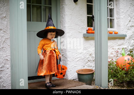 Toddler girl dressed up playing in Halloween party - Stock Photo