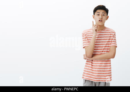 Asian cute guy making assemption adding suggestion or asking question while attending interesting lecture raising index finger open mouth and looking at camera interested - Stock Photo