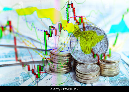 financial and investment concept -  trade chart over silver dollar coin on US Dollar bills and heap of golden coins - Stock Photo