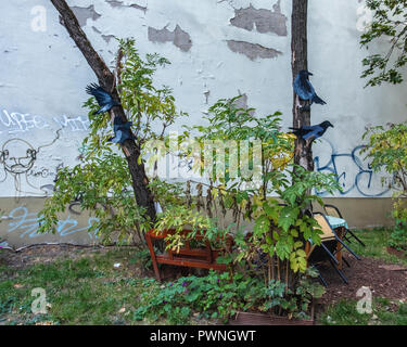 Berlin, Mitte. Painted paper birds in tree in Children's play area between buildings with weathered old wall - Stock Photo