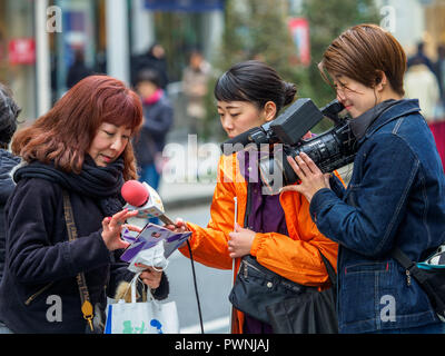 Ginza Shopping Video - Japanese TV crew interview shoppers in the Ginza Shopping district in Tokyo Japan - Stock Photo