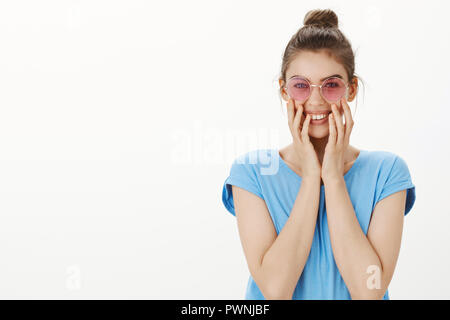 Oh stop it you. Portrait of tender feminine and stylish woman in trendy pink glasses, smiling joyfully and holding palms on cheeks, being charmed and happy, blushing from compliments - Stock Photo