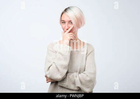 Cunning beautiful woman with dyed short hair looking holding hand under chin intending to realize tricky plan. - Stock Photo