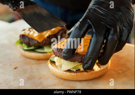 The chef prepares a burger in the open air kitchen. Street fast food. Sunset light. - Stock Photo
