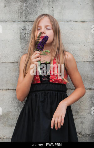 Young girl in a lovely dress, holding a flower - Stock Photo