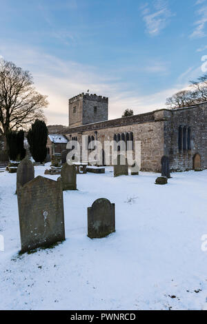 Snowy winter exterior of St Michael and All Angels Church with headstones in snow-covered churchyard - Hubberholme, Yorkshire Dales, England, UK. - Stock Photo