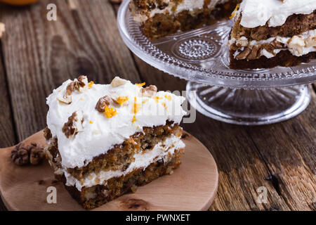 Carrot orange layer cake with cream cheese frosting on rustic wooden table - Stock Photo