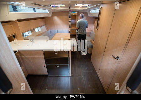 Giebelstadt, Bavaria. 17th Oct, 2018. An employee of the Bavarian boat builder Bavaria Yachtbau works in the production of the company inside a ship. Credit: Daniel Karmann/dpa/Alamy Live News - Stock Photo