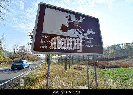 17 October 2018, Thuringia, Ifta: 17 October 2018, Germany, Ifta: A sign with the inscription 'Germany and Europe were divided here until 18 November 1989 at 6 a.m.' stands on the former inner-German border. In Thuringia, the delegation from South Korea is learning how a death strip became a protected area for plants and animals. The currently demilitarised zone between North and South Korea is 248 kilometres long and about four kilometres wide. Thuringia's Green Belt has a length of 763 kilometres, out of a total of 1400 kilometres in Germany. Photo: Martin Schutt/dpa-Zentralbild/dpa - Stock Photo