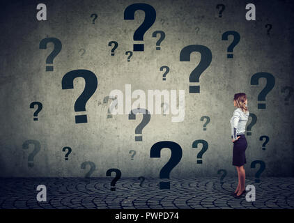 Rear view of young business woman with hand on head standing in front of a wall with many questions wondering what to do next. Businesswoman facing ch - Stock Photo
