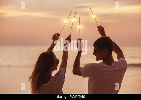 Happy couple having fun and celebrates sunset with sparklers in hands - Stock Photo