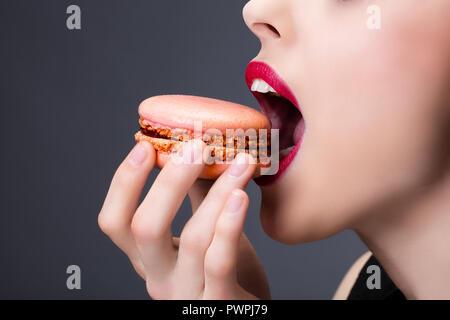 Tight shot of a girl enjoying a macaroon