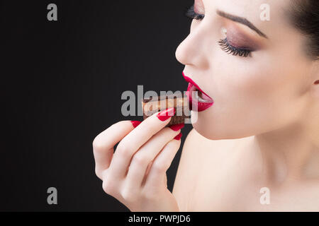 Tight shot of girl tasting chocolate cake - Stock Photo