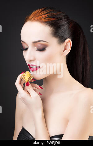 Tight shot of a girl enjoying a lemon cake - Stock Photo