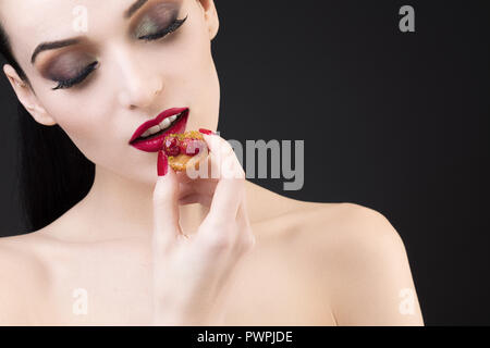 Tight shot of girl tasting red fruit tart - Stock Photo