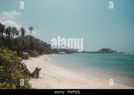 Pristine white sand beach of Tayrona National Park surrounded by jungle on the Caribbean coast of Colombia - Stock Photo