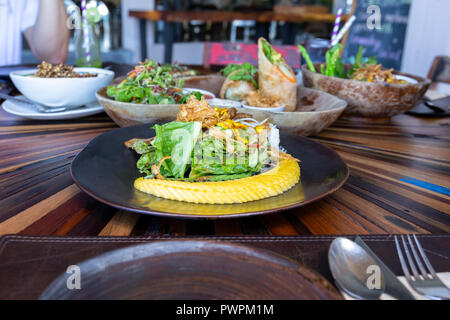 Healthy clean eating vegetables salad on plate with fresh ripe mango. - Stock Photo