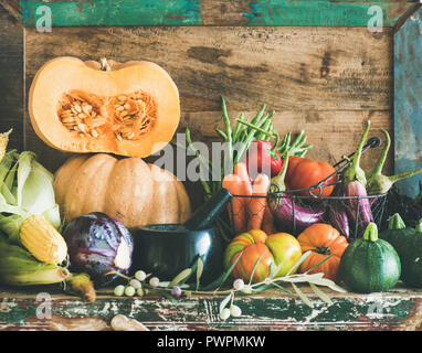 Fall vegetarian food ingredient variety. Assortment of various Autumn vegetables for healthy cooking over rustic cupboard, wooden tray background. Loc - Stock Photo