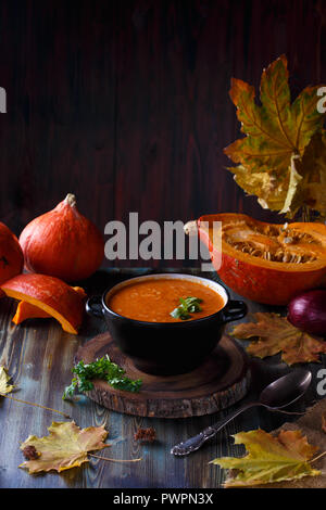Pumpkin soup puree with greens in a plate on a dark table. On the background of pumpkins Menu and restaurant concept Copy space - Stock Photo