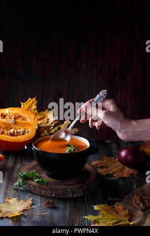 Female hand stir pumpkin soup puree with greens in a plate on a dark table. On the background of pumpkins Menu and restaurant concept Copy space
