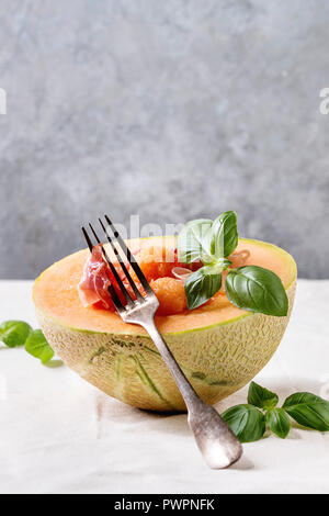 Melon and ham or prosciutto salad served in half of Cantaloupe melon, decorated by fresh basil standing on white tablecloth with fork. - Stock Photo