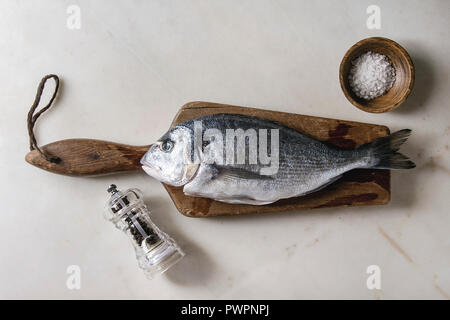 Raw uncooked gutted sea bream or dorado fish on wooden cutting board with ice, salt and pepper over white marble background. Flat lay, copy space. Coo - Stock Photo