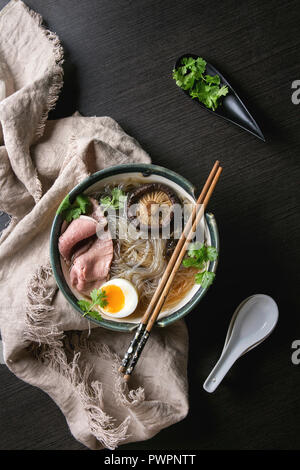 Traditional Japanese Noodle Soup with shiitake mushroom, egg, sliced beef and greens served in ceramic bowl with wooden chopsticks and white spoon on  - Stock Photo