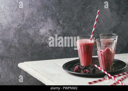 Red fruit berries watermelon iced cocktail and frozen juice sorbet in glasses with striped straw stand on metal tray on white marble table with grey w - Stock Photo
