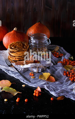 Autumn concept. Pumpkin pancakes with caramel topping, with pumpkins, leaves on a dark background. Close up - Stock Photo