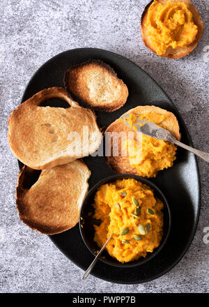 Roasted pumpkin dip with slices of toast on a serving dish. - Stock Photo
