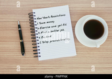 New Year's Resolutions text on notepad - pen and coffee - Stock Photo