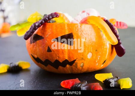 Trick or treat Halloween concept with pumpkin Jack with various candies on black table - Stock Photo