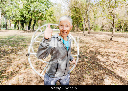 Portrait Of Happy Healthy Senior Woman Workout At Outdoor Gym In Nature. Showing Thumb Up With Big Smile. - Stock Photo