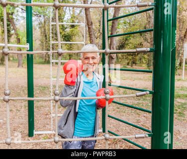 Portrait Of Happy Fit Senior Woman With Boxing Glove At Outdoor Gym In Sportswear. Active Old People Fitness Lifestyle - Stock Photo