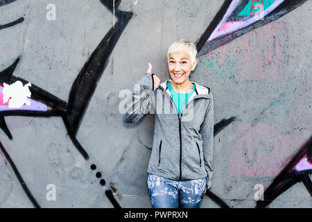 Happy Mature Woman Relax After Running, Showing Thumb Up, Leaning On The  Wall. Short Hair, Sports Clothes , Looking At The Camera - Stock Photo
