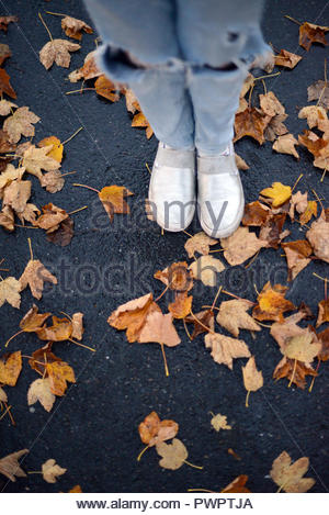 a girl standing on an asphalt by a puddle with scattered colorful autumn leaves - Stock Photo