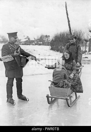 Skating mail man. A properly dressed mailman in uniform is delivering the post when skating on the ice. A woman sitting in a sledge reaches for her post. 1930s. - Stock Photo