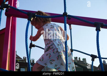 Climbing activities on the children playground. A little girl playing on a playground - Stock Photo