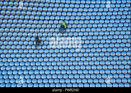 Cleaners suspended by ropes on the outside of Selfridges department store in the Bull Ring, Birmingham - Stock Photo