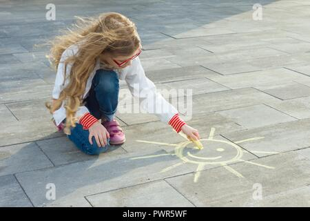 Child girl draws the symbol of the sun with colored crayons on the asphalt. - Stock Photo
