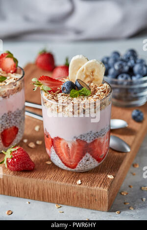 Dietary natural breakfast with fresh organic ingredients - berries, granola, banana in a glass on a wooden table. Healthy vegetarian eating. - Stock Photo