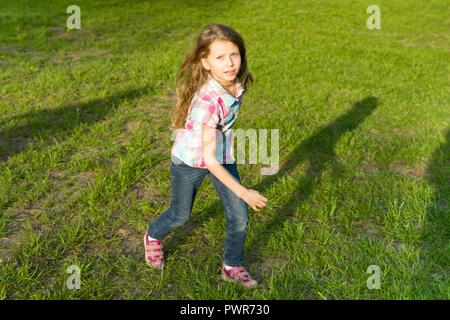 Running little girl in the park, the child is having fun, playing and running on the green lawn. - Stock Photo