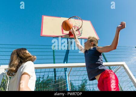 Streetball basketball game with two players, teenagers girl and boy, morning on basketball court. - Stock Photo