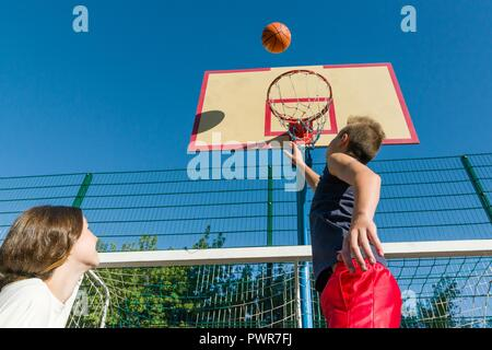 Streetball basketball game with two players, teenagers girl and boy, morning on basketball court - Stock Photo