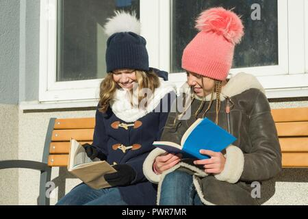 Winter portrait of cheerful young friends students on a bench with books, positive people and friendship concept - Stock Photo