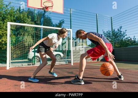 Streetball basketball game with two players, teenagers girl and boy, day on basketball court. - Stock Photo