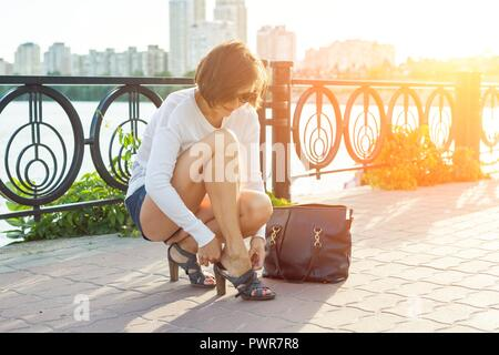 Outdoor summer portrait of mature woman in sunglasses with a bag and straightening shoes in the evening sunny city. - Stock Photo